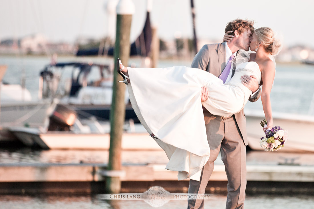 Beach Wedding Picture - Groom holding his bride on a dock.  Wrightsville Beach Wedding Photographers